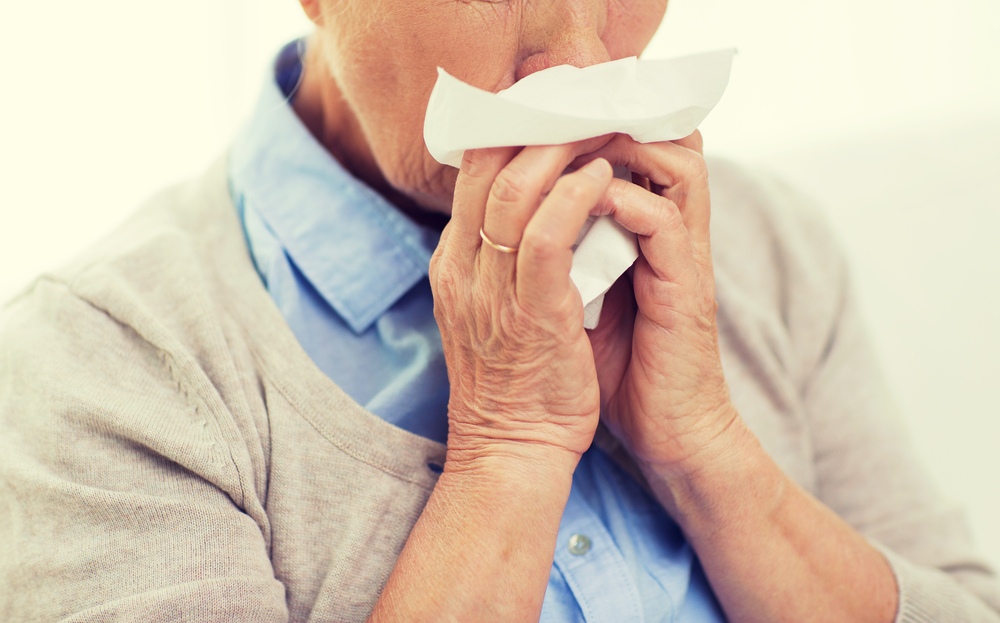 Elderly woman sneezing