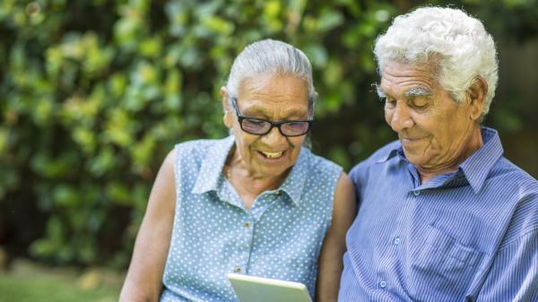 elderly couple reading computer tablet alternative angle